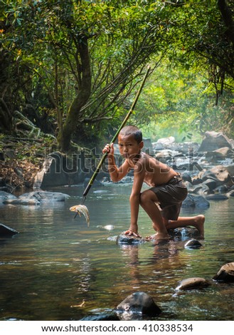 Fisher boy hunter fishing gaff on the creek forest. #410338534