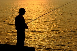 fisher in golden sunshine with beautiful sea