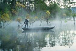Fisher man with wooden boat at Tuyen Lam lake, Da Lat, Vietnam