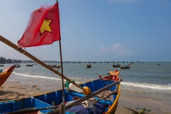 Fisher men boat at the east coast of Vietnam near the city of Nha Trang, with the national flag of Vietnam. Hundreds of small boat cruising at the shoreline and catching fish under the blue sky