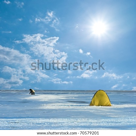 fisher on a frozen river under a sparkle sun - stock photo