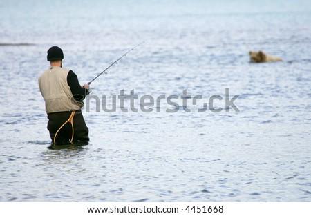 Fisherman and bear fishing for salmon, Katmai National Park, Alaska