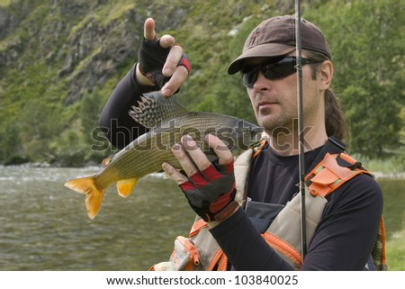 Fisherman and the catch. A fisherman in a professional outfit holding a large grayling