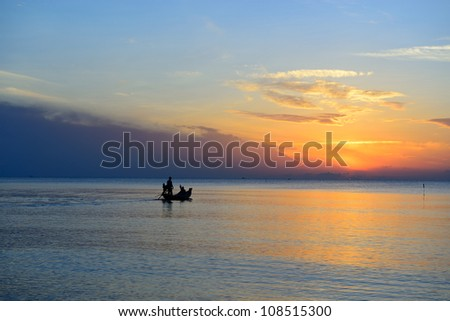 Fisherman are taking fishing boat to fish with sunrise background in thailand