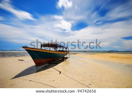 Fisherman boat on low tide shore