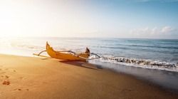 Fisherman boat. Sunrise landscape. Traditional Balinese boat jukung. Fishing boat at the beach. Water reflection. Sanur beach, Bali, Indonesia.