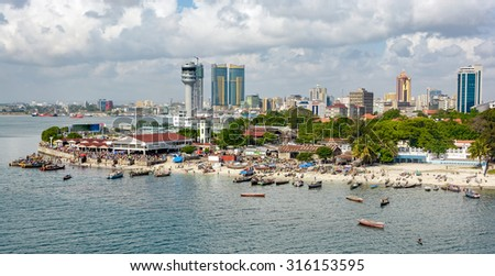 Fisherman boats in front of Kivukoni fish market with Port control tower and Skyscrapers Behind, Dar Es Salaam, Tanzania Foto stock ©