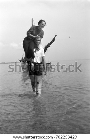 Fisherman carrying woman on his shoulder at low tide