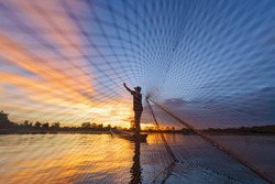 Fisherman casting his net on during sunrise.Silhouette Asian fisherman on wooden boat casting a net for freshwater fish