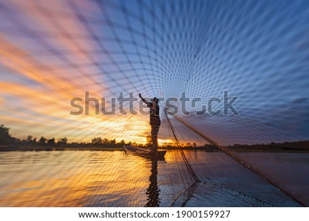 Fisherman casting his net on during sunrise.Silhouette Asian fisherman on wooden boat casting a net for freshwater fish Foto stock ©