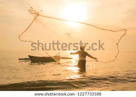 fisherman casting net during sunrise. Fishing and outdoor activities concept. selective focus. #1227733588