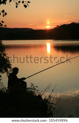Fisherman catches fish. He was in the background the lake with. Silhouette - stock photo