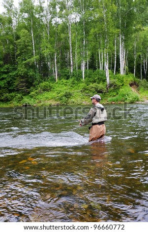 Fisherman catches of salmon and trout in a mountain river.