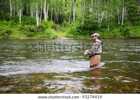 Fisherman catches of salmon and trout in the river.