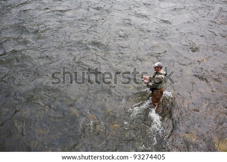 Fisherman catches of salmon on a mountain river