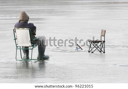 Fisherman catching a fish on a frozen lake in winter.