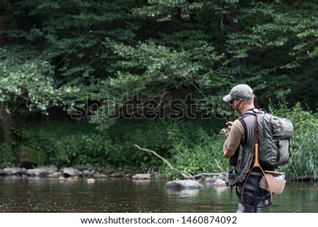 Fisherman catching trout on spinner #1460874092