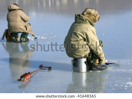 fisherman caughts fishing rod fish from under ice