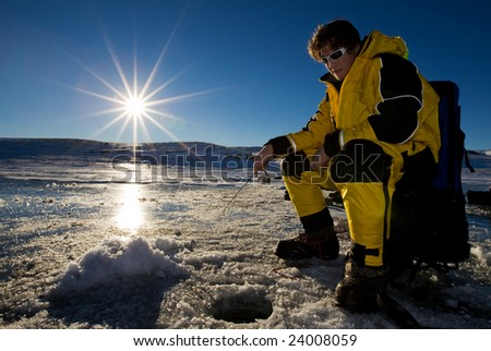 Fisherman enjoying a day on the ice with a low setting sun