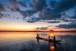 Fisherman family are flying lantern on the boat in the lake at sunset