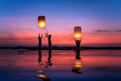 Fisherman family are flying lantern on the boat in the Mekong river During the twilight at beautiful sunset, silhouette with copy space.