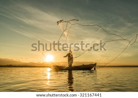 Fisherman fishing at lake in Morning, Thailand. #321167441