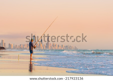 Fisherman fishing at sunrise on the Gold Coast with Surfers Paradise in the background.