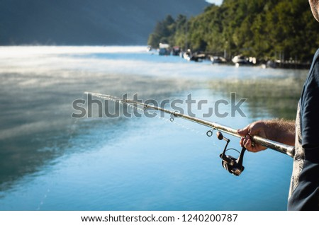 Fisherman fishing in a sea with morning mist on a water surface #1240200787
