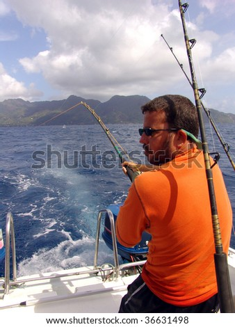 Fisherman fishing on boat in ocean on Seychelles
