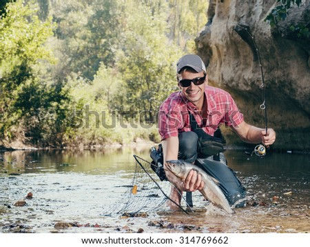 Fisherman. Fishing on the river fly fishing. Man fisherman holds in hand large catch fish.