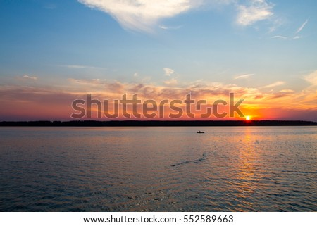 Fisherman floats on a lake at sunset #552589663