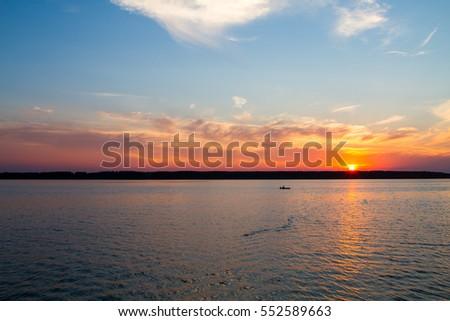 Fisherman floats on a lake at sunset #552589663