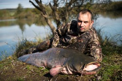 Fisherman holding a giant catfish. Catch of fish, freshwater fishing, monster fish