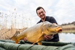 Fisherman holding a huge carp at the lake.