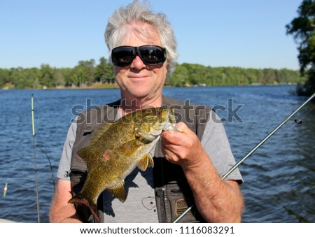 Fisherman holding a Smallmouth Bass with a blue sky and lake as the background #1116083291