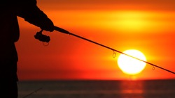 Fisherman holding fishing pole fishing off pier at sunrise in silhouette.