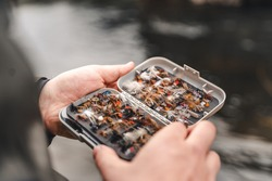 Fisherman holding fly fishing lures box in hands