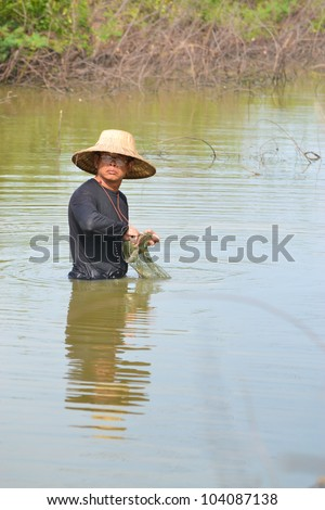 fisherman hunting fish in countryside pond by purse seine of Thailand southeast asia - stock photo