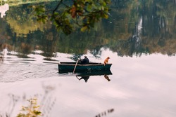 fisherman in a boat with a dog