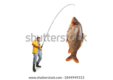 Fisherman in a yellow raincoat catching a big fish isolated on white background Foto stock ©