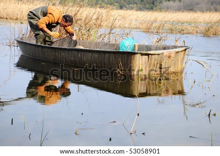 fisherman in boat on lake
