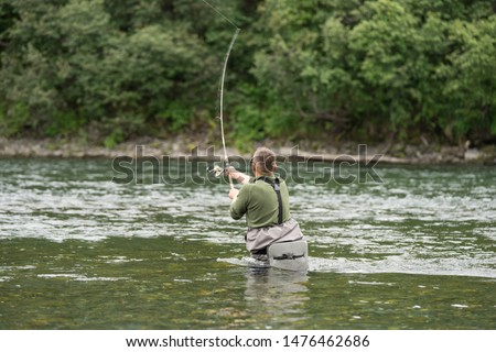 Fisherman in Bystraya River in Kamchatka. Man in special rubber equipment angling in the middle of the stream. He throws trolling spoon and hopes to catch some fish. Greenery around him. Russia.