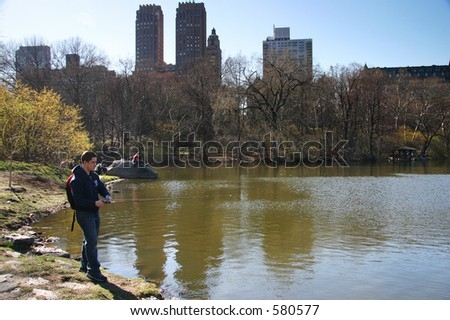 Fisherman in Central Park, NY at a pond.  The NY Skyline is behind him.