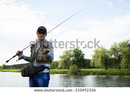Fisherman in professional gear on the river bank. Fisherman catching fish and holds it in his hand. Pike, fish, fishing, nature, fishing rod - the concept of leisure. Article about fishing. #210492106
