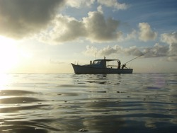 Fisherman on a boat off the south shore of Guam at sunset