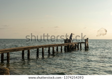 Fisherman on a jetty throwing his fishing net with the sky and horizon in background, picture from Phu Quoc Island, Vietnam.
