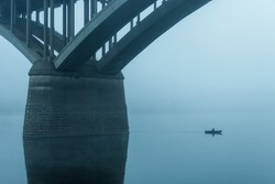 fisherman on a small boat sails next to the pillars of the bridge in the fog