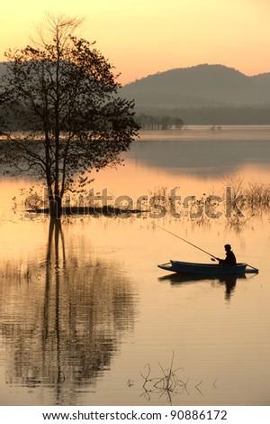 Fisherman on big lake in morning .