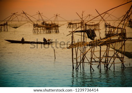 Fisherman on boat with fishing traps ,square dip net in lake is local fishery with vintage scenery vintage sunrise or sunset at Pakpra Phatthalung in famous tourist to travel at southern of Thailand.