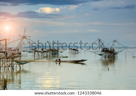 Fisherman on boat with fishing traps ,square dip net in lake is local fishery with vintage scenery sunrise or sunset at Pakpra Phatthalung in famous tourist to travel at southern of Thailand.